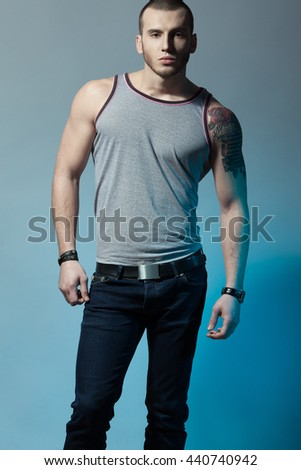 Portrait of tattooed brutal young man with short hair and bristle on face wearing sleeveless shirt, jeans, posing over blue & gray background. Bully style. Studio shot - stock photo