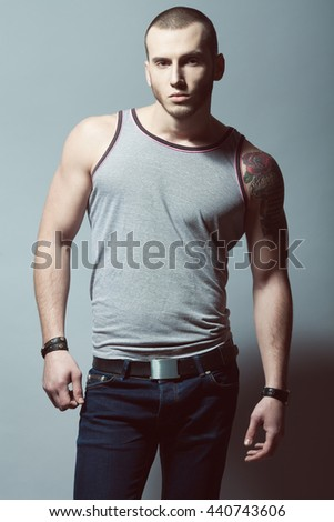 Portrait of tattooed brutal young man with short hair and bristle on face wearing sleeveless shirt, blue jeans and posing over gray background. Bully style. Studio shot