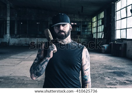 Portrait of tattooed man with the hammer in his hands,selective focus  - stock photo