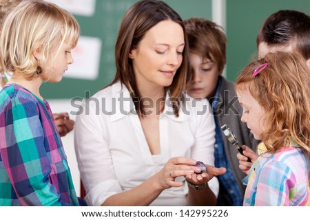 Portrait of teacher explaining something to her students - stock photo