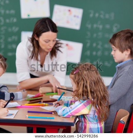 Portrait of teacher helping her busy students inside the classroom - stock photo