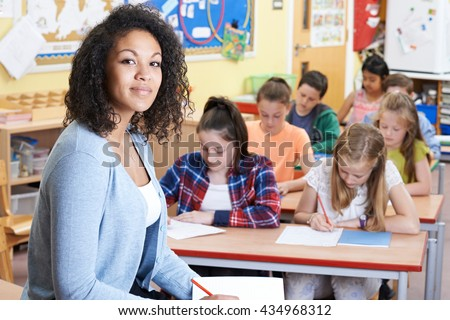 Portrait Of Teacher In Class With Pupils - stock photo
