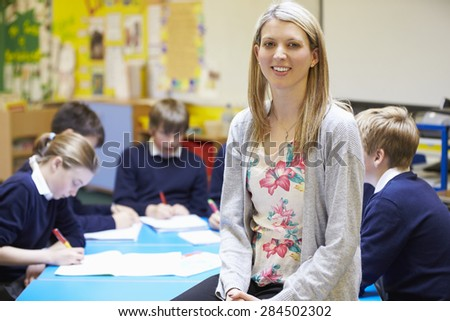 Portrait Of Teacher In Classroom With Pupils - stock photo