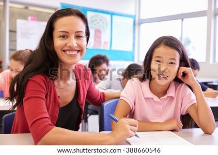 Portrait of teacher with elementary school girl at her desk - stock photo