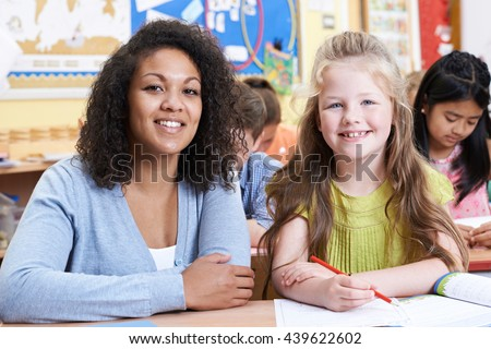 Portrait Of Teacher With Female Elementary School Pupil In Class