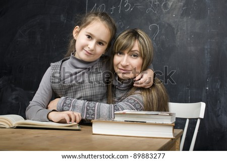portrait of teacher with pupil at blackboard - stock photo