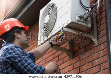 Portrait of technician in hardhat connecting outdoor air conditioning unit - stock photo