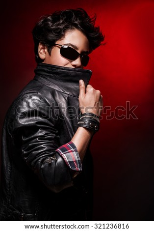 Portrait of teen boy wearing stylish leather jacket and sunglasses posing in the studio over dark red background, fashion for adolescents