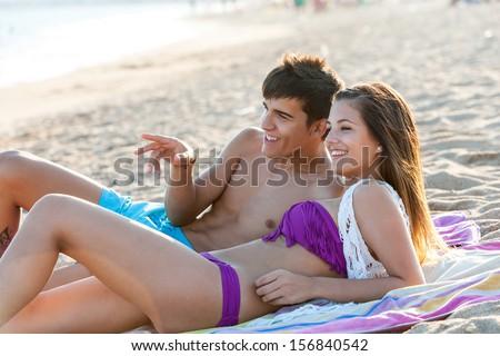 Portrait of teen couple enjoying late afternoon sun on beach. - stock photo