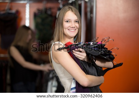 Portrait of teen girl posing with new clothes. Happy smiling friendly looking young beautiful woman shopping, going to fitting room in fashion mall, holding bunch of hangers with different dresses - stock photo