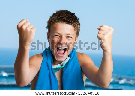 Portrait of teen swimmer with victorious face reaction.
