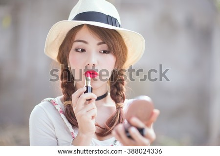 portrait of teenage asian girl applying lipstick, focus on mouth.