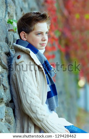 portrait of teenage boy at brick wall, outdoors - stock photo