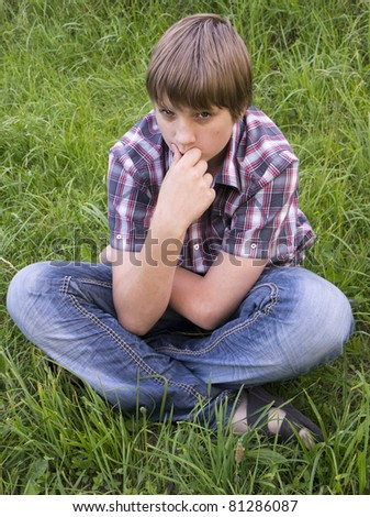 Portrait of teenage boy on the grass background - stock photo