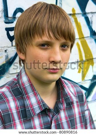 Portrait of teenage boy on the trees background - stock photo