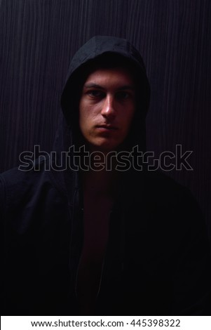 Portrait of teenage boy with serious expression and black hoodie on his head, brown dark hair, direct gaze. Dark background, lights and shadows