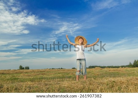 Portrait of teenage farmer on harvested cereal field - stock photo