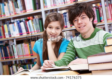Portrait of teenage girl and her classmate looking at camera in library - stock photo