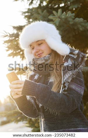 Portrait of teenage girl holding mobile phone outside in winter - stock photo