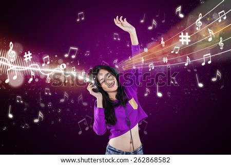 Portrait of teenage girl singing and dancing while listening music with headphones - stock photo
