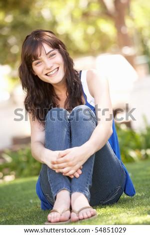 Portrait Of  Teenage Girl Sitting In Park - stock photo