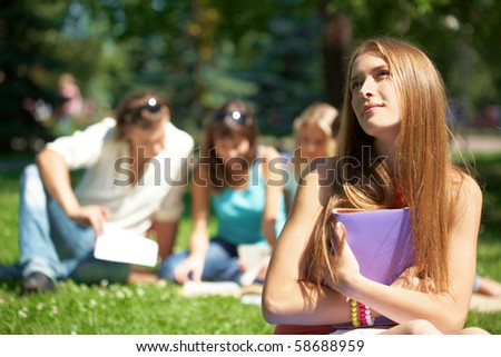 Portrait of teenage girl with book in hands on background of her reading friends - stock photo