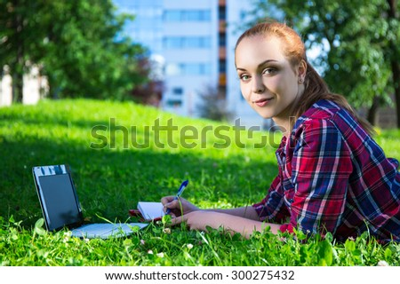portrait of teenage student or school girl lying in park with laptop