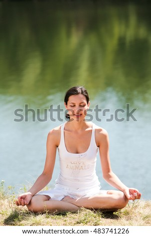 Portrait of teenager meditating on green grass near lake in summer