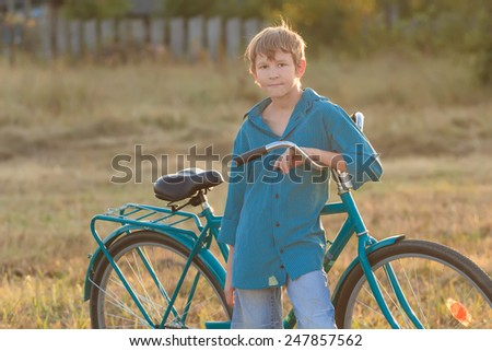 Portrait of teenager with a blue bike in farm field - stock photo