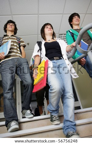 Portrait of teenagers coming down stairs holding documents - stock photo