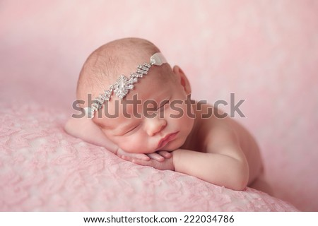 Portrait of ten day old newborn baby girl. She is wearing a rhinestone headband and is sleeping on light pink lace material. - stock photo