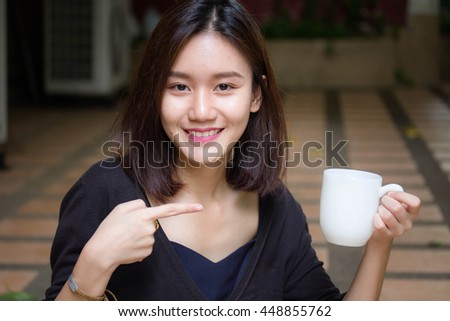 Portrait of thai adult beautiful girl drinking coffee - stock photo