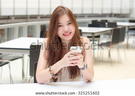 Portrait of thai adult beautiful girl using her smart phone and smile.