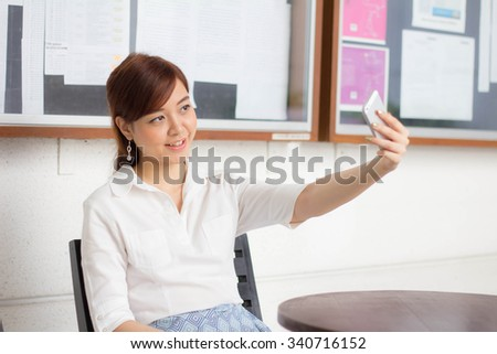 Portrait of thai adult businesswoman beautiful girl using her smart phone Selfie.
