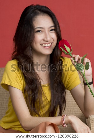 Portrait of Thai beautiful young woman sitting on red background smelling roses.