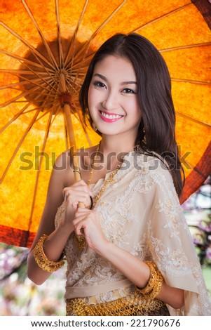 Portrait of Thai young lady in Sakura Garden in Thailand dance wea with Umbrella. - stock photo