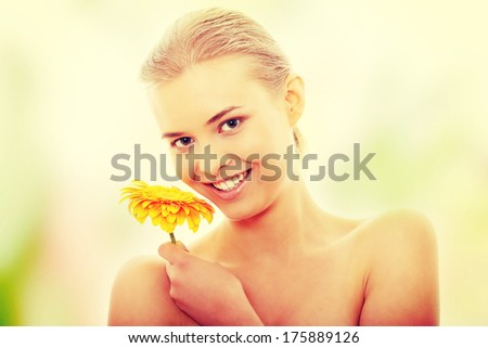 Portrait of the attractive girl without a make-up, with flower in hand - stock photo