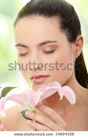 Portrait of the attractive girl without a make-up, with lily flower in hand - stock photo