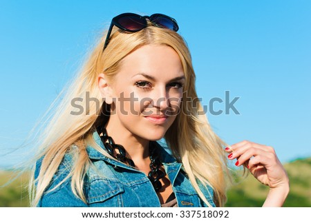 portrait of the attractive, slender, beautiful young Caucasian  blonde girl in a jeans jacket. Smiling girl enjoys fine warm summer weather highly in mountains against the sea - stock photo