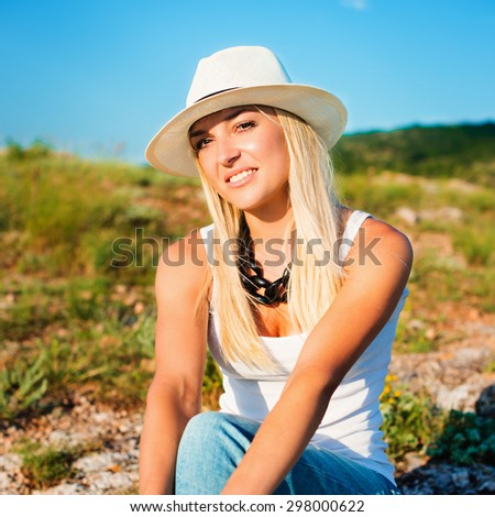 portrait of the attractive, slender, beautiful young Caucasian  blonde girl in a stinny hat. Smiling girl enjoys fine warm sunner weather highly in mountains. instagram - stock photo