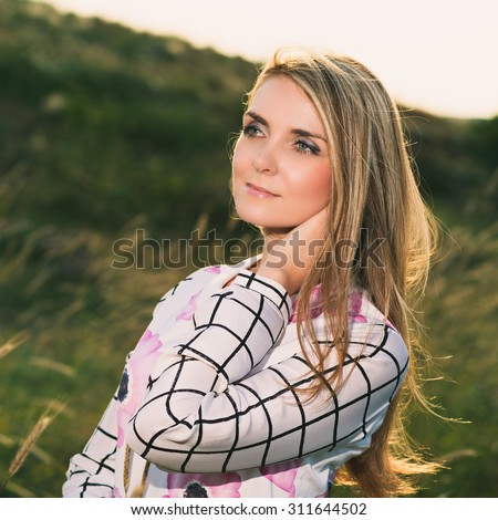 portrait of the attractive, slender, beautiful young Caucasian  blonde girl outdoor. Beautiful modern woman  with the long developing fair hair in a loose dress. dressy style. snub nose. instagram - stock photo