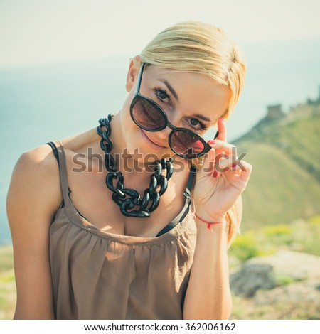portrait of the attractive, slender, beautiful young Caucasian  blonde girl. Smiling girl enjoys fine warm summer weather. Photo with instagram style filters - stock photo