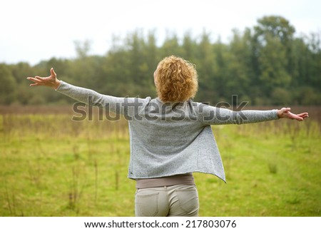 Portrait of the back of a carefree woman with arms spread open outdoors - stock photo