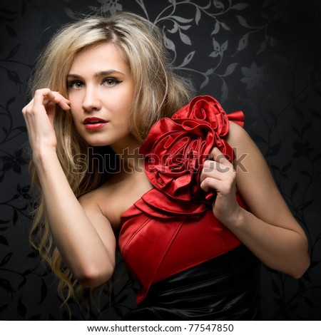 Portrait of the beautiful blonde in a red evening dress - stock photo