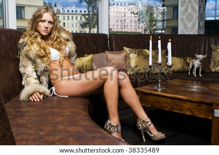 Portrait of the beautiful blonde. She is sitting in the restaurant with her dog - stock photo