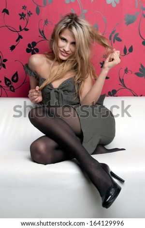 Portrait of the beautiful blonde. She is sitting on the sofa - stock photo