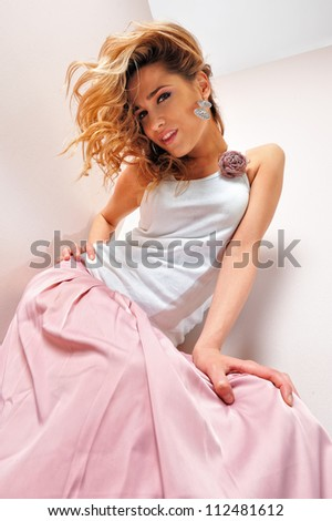 Portrait of the beautiful blonde woman in pink scirt. Studio shoot. - stock photo
