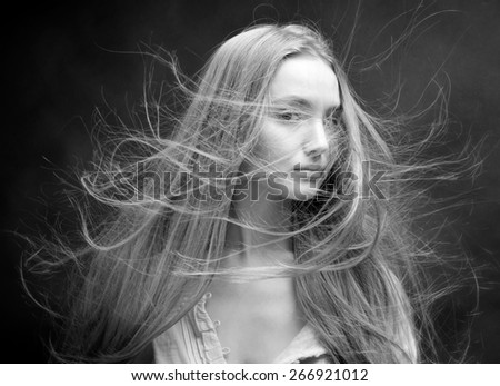 Portrait of the beautiful blonde woman with flying long hair. She is in studio . Monochrome image - stock photo