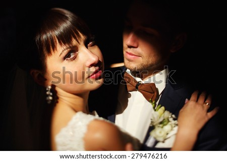 Portrait of the beautiful bride in wedding dress on a dark background - stock photo
