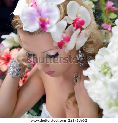 Portrait of the beautiful chic woman around the flowers. - stock photo